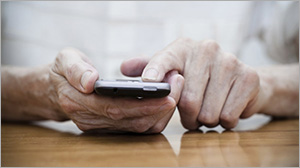 Older hands on a cell phone