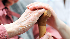 Close up of elder and younger female hands resting on top of a cane.