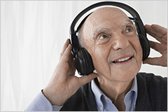 Elderly man listening to music with a headset on.