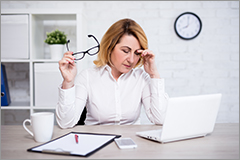 Middle-aged woman holding glasses while looking distraughtly at her computer.