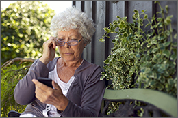 Grandmother sitting on a bench looking at her cell phone.