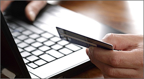 Photo illustration of laptop and hand holding credit/debit card.