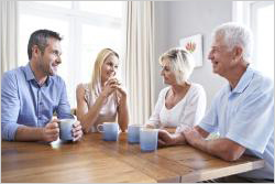 Elderly couple and younger couple sitting at a table having coffee