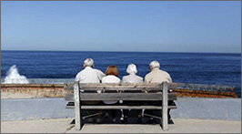 Elderly couples sitting on a bench with the ocean in front of them