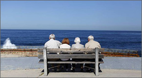 Two senior couples sitting on a bench facing the ocean
