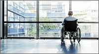 Man in wheelchair looking out a glass wall of windows