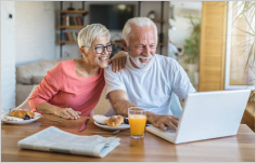 Couple at table looking at laptop