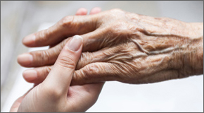Young person holding an elder's hand