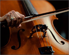 Close up of cello with hand holding a bow